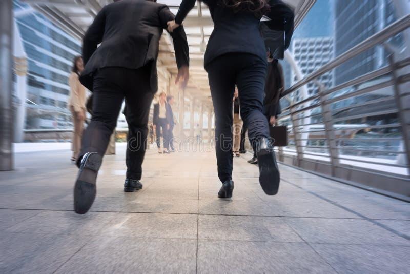 Affärsmannen och kvinnan skynda sig upp och köra i affärsstadsstre arkivfoton