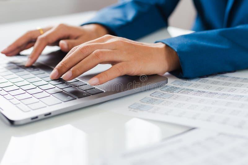 Affärsmannen räcker den upptagna användande bärbara datorn på kontorsskrivbordet royaltyfria foton