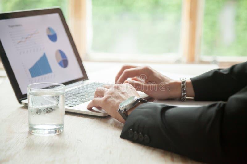 Affärsmannen räcker genom att använda PCbärbara datorn som arbetar med statistik, clos royaltyfri bild