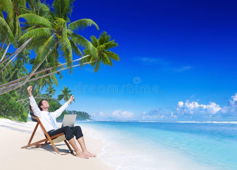 Affärsmannen Relaxing på ett idylliskt gömma i handflatan den satte fransar på stranden royaltyfria foton