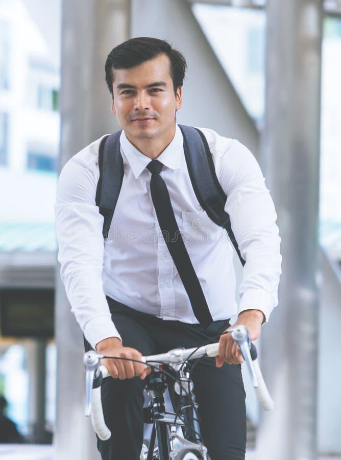 Affärsmannen rider cykeln för att arbeta i staden arkivfoto