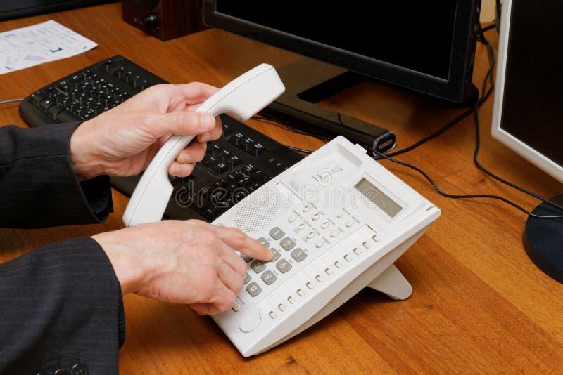 Affärsmannen ringer ett telefonnummer royaltyfri fotografi