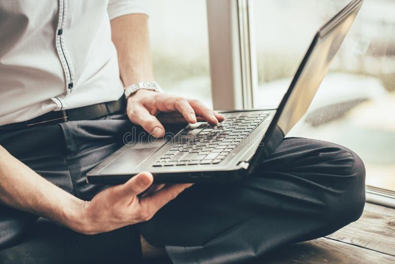 Affärsmannen rymmer en bärbar dator på hans ben och arbeten bak honom på fönstret under dagen på huset fotografering för bildbyråer