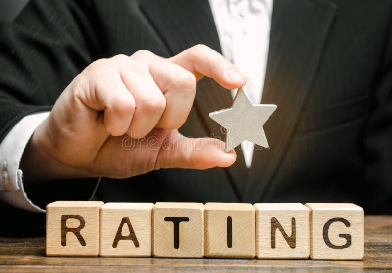 Affärsmannen rymmer en stjärna ovanför träkvarteren med ordvärderingen Begrepp av negativ återkoppling Låg kvalitet och service arkivbild