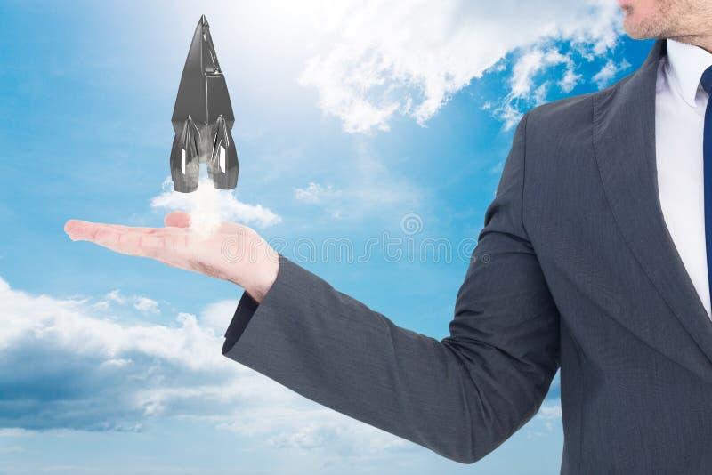 Affärsmannen rymmer raket som tar av från hans hand mot himmelbakgrund royaltyfria foton