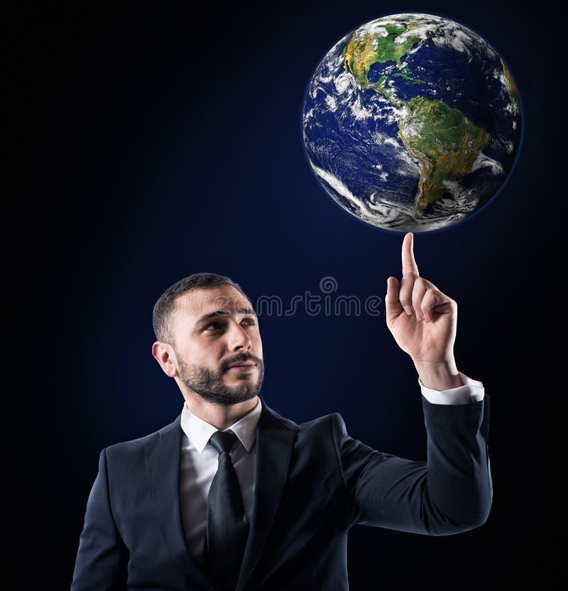 Affärsmannen rymmer världen med ett finger värld förutsatt att av nasa royaltyfria foton