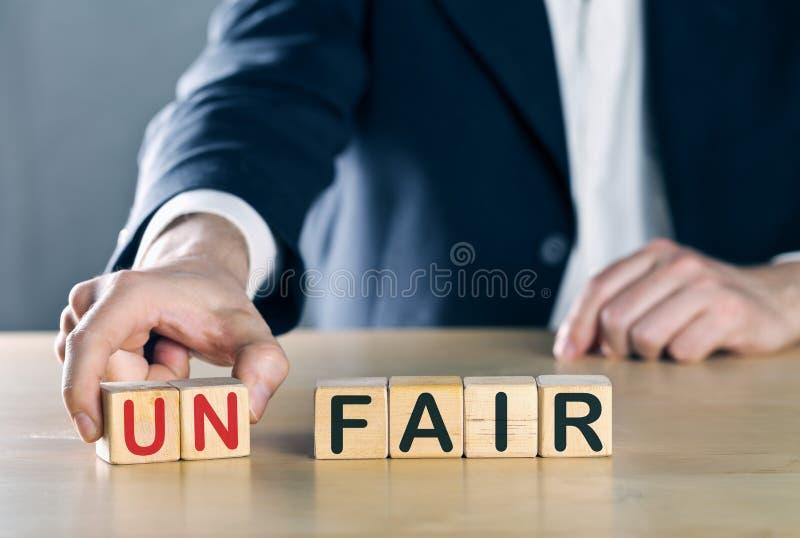 Affärsmannen sätter bort första två bokstäver från det orättvisa ordet, så det blir ganska; sportar eller affärsrent spelbegrepp fotografering för bildbyråer