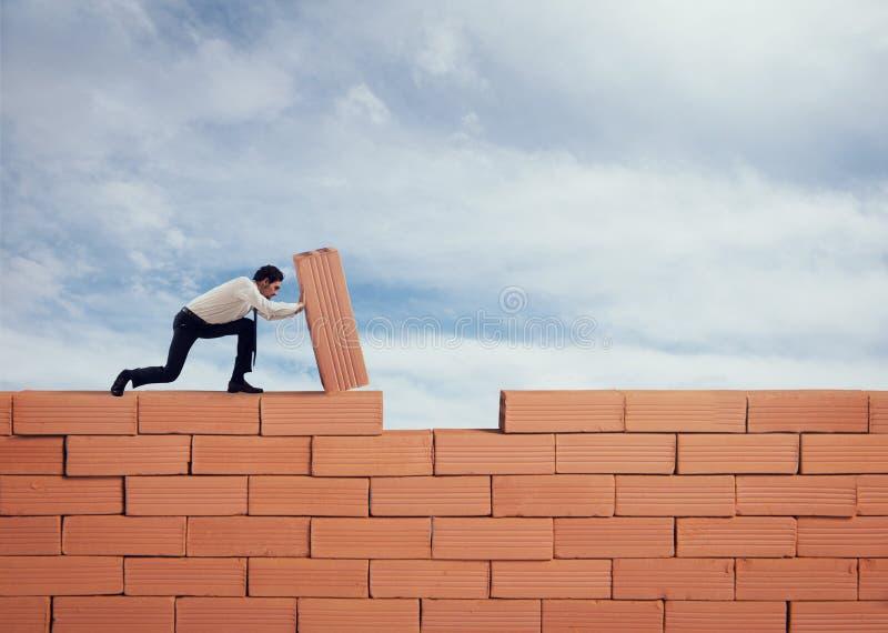 Affärsmannen sätter en tegelsten för att bygga en vägg Begrepp av den nya affären, partnerskap, integration och starten arkivfoto
