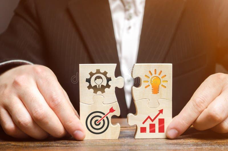 Affärsmannen samlar pussel med bilden av attributen av att göra affär Strategiplanläggningsbegrepp Organisation av fotografering för bildbyråer