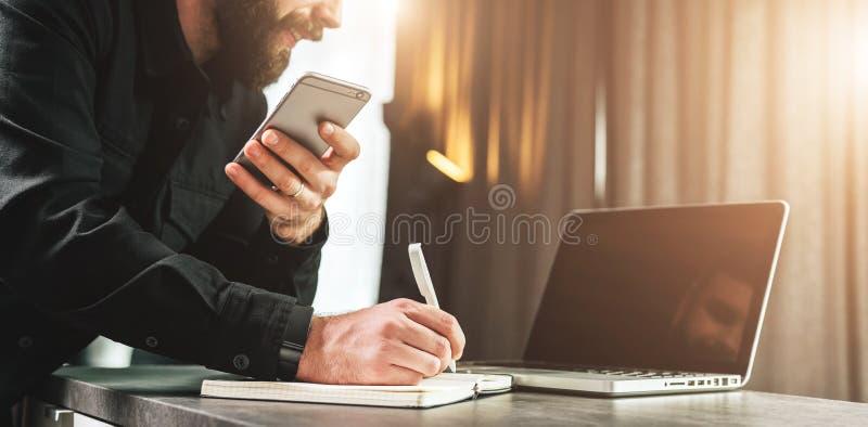 Affärsmannen ser bärbar datorskärmen som gör en anmärkning i anteckningsbok, medan rymma smartphonen Entreprenören analyserar inf arkivbild