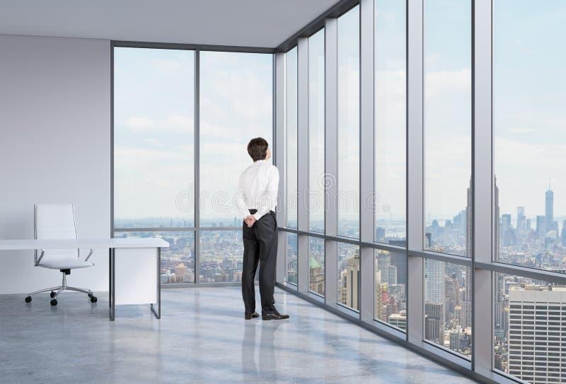Affärsmannen ser till och med hörnfönstret bakgrund New York royaltyfri fotografi