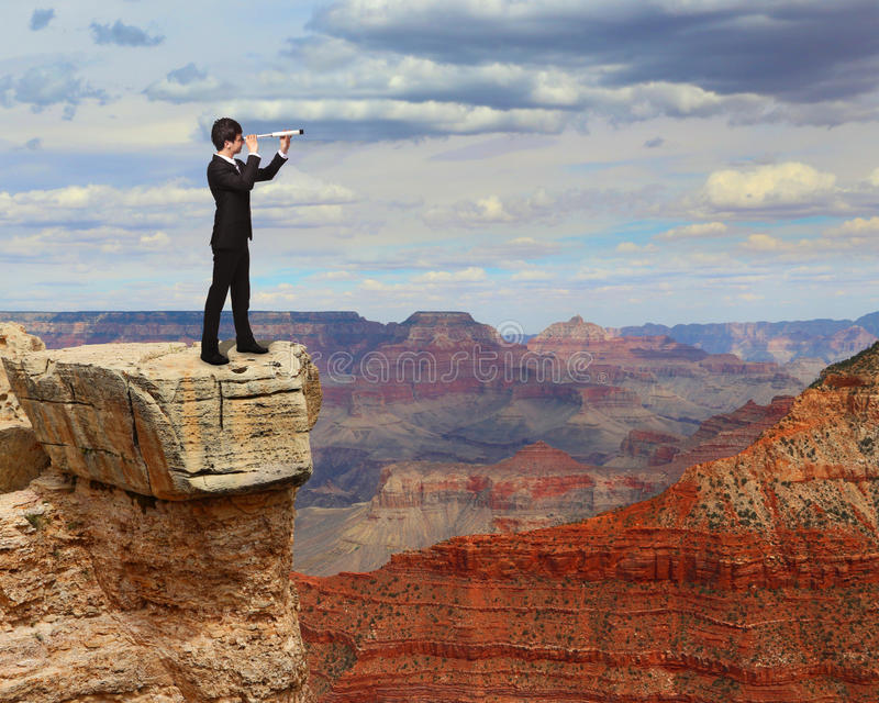 Affärsmannen ser till och med teleskopet på berget royaltyfri fotografi