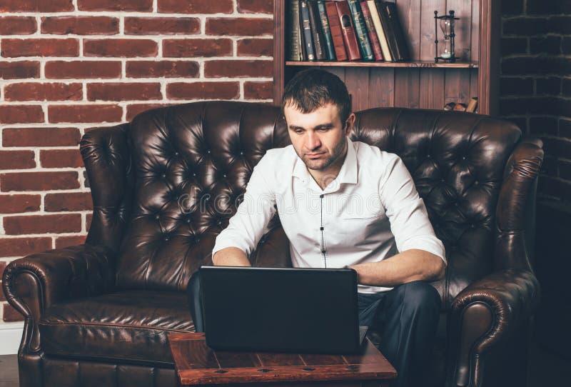 Affärsmannen sitter på en lädersoffa bak en bärbar dator på bakgrunden av ruminre En man arbetar i eget kabinett royaltyfria bilder