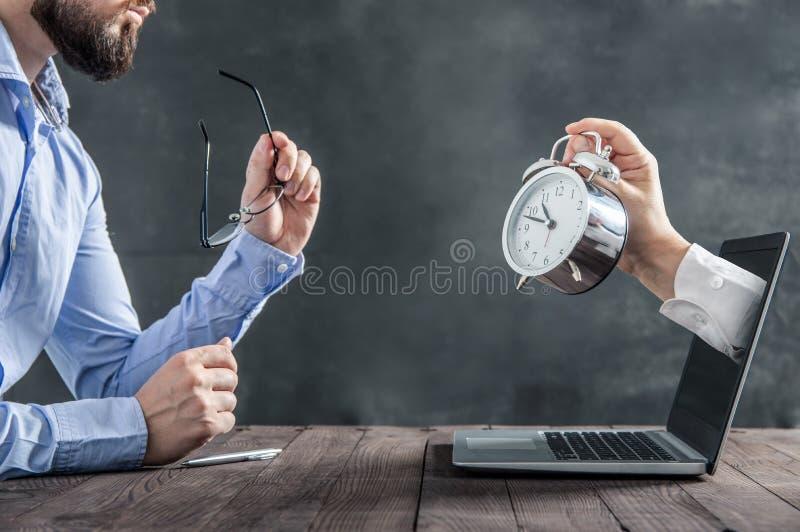 Affärsmannen sitter på skrivbordet och ser klockan royaltyfri foto