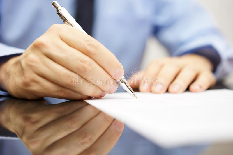 Affärsmannen skrivar ett brev eller undertecknar en överenskommelse royaltyfria foton