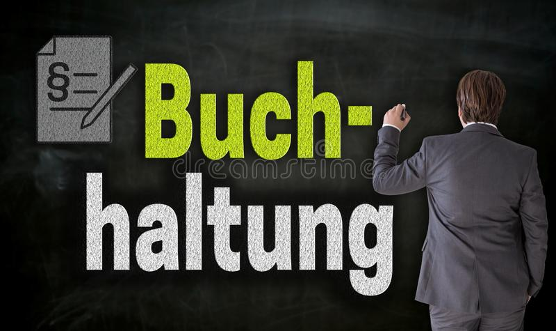 Affärsmannen skriver med krita Buchhaltung i tysk redovisning på svart tavla arkivfoto