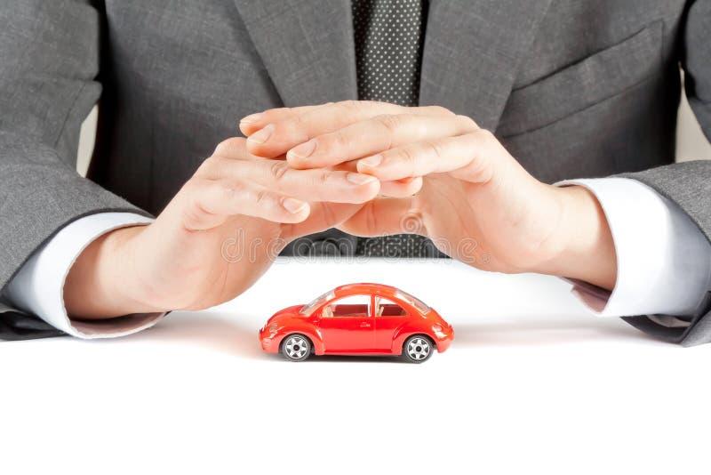 Affärsmannen skyddar med hans händer en röd bil, begreppet för försäkring, köpande, att hyra, bränsle eller service och reparation arkivfoto