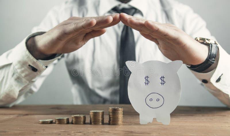 Affärsmannen skyddar pappersspargrisen och mynt coins sparande f?r stapel f?r begreppshandpengar skyddande arkivbild