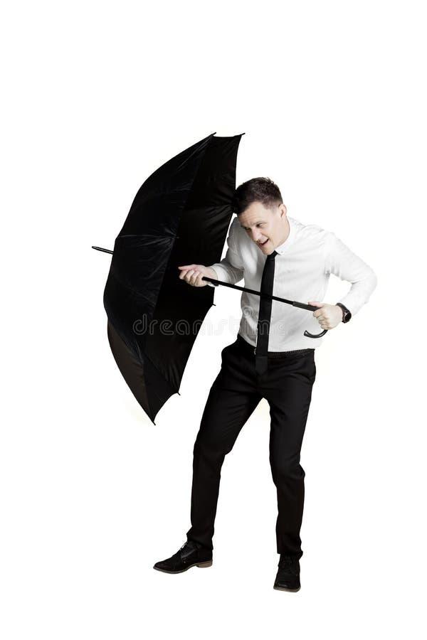 Affärsmannen skyddar sig med ett paraply royaltyfria bilder