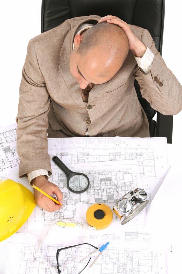 Affärsmannen som är tänkande med arkitektoniskt, planerar