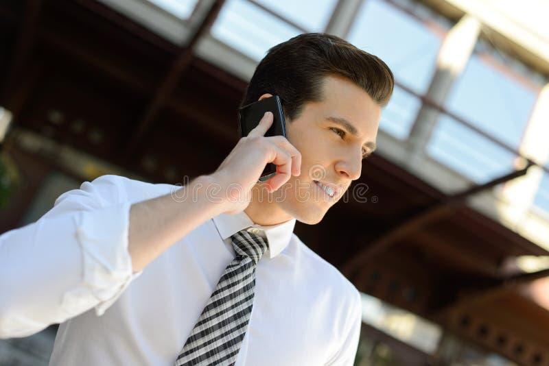 Affärsmannen som använder ett smart, ringer i en kontorsbyggnad arkivfoton