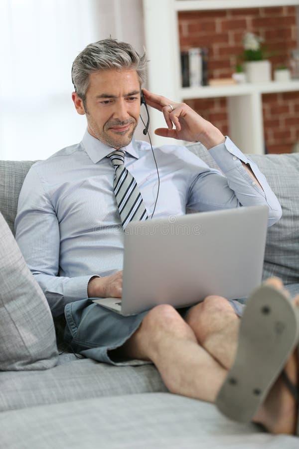 Affärsmannen som arbetar på bärbara datorn, kopplade av på soffan arkivbilder