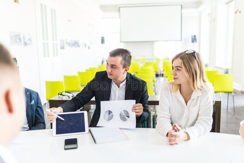 Affärsmannen som arbetar på kontoret med bärbara datorn, och dokument introducerar resultaten av projektet till laget Teamworksam royaltyfri fotografi