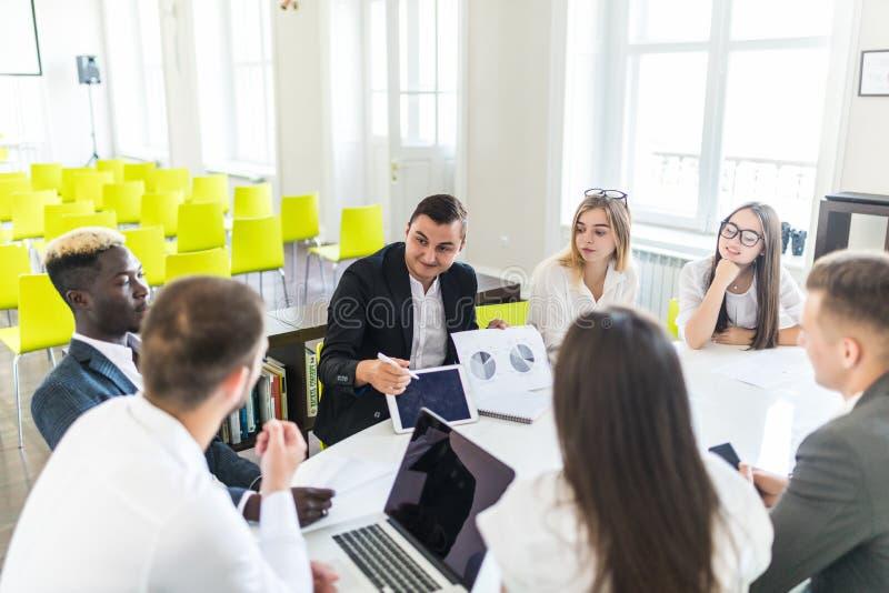 Affärsmannen som arbetar på kontoret med bärbara datorn, och dokument introducerar resultaten av projektet till laget Teamworksam arkivfoton