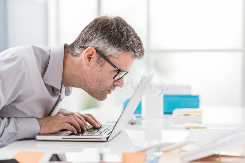 Affärsmannen som arbetar på kontorsskrivbordet, är han stirrig på bärbar datorskärmslutet upp och rymma hans exponeringsglas, arb royaltyfria bilder