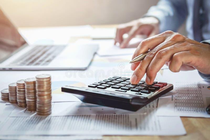 affärsmannen som arbetar på skrivbordet med att använda räknemaskinen för, beräknar finans och redovisning royaltyfri foto