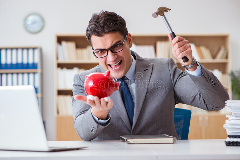 Affärsmannen som bryter piggybank i kontoret arkivbild