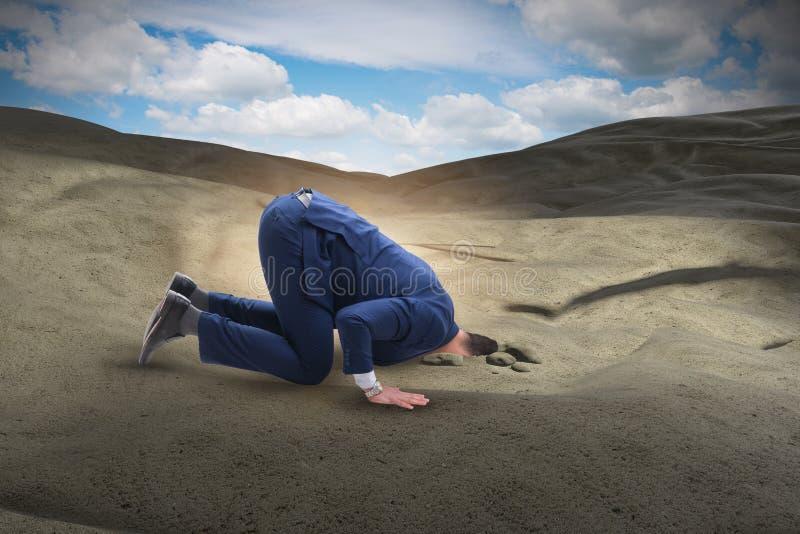 Affärsmannen som döljer hans huvud i sand som flyr från problem royaltyfria bilder