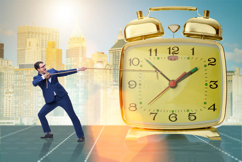 Affärsmannen som drar klockan i begrepp för tidledning arkivbild