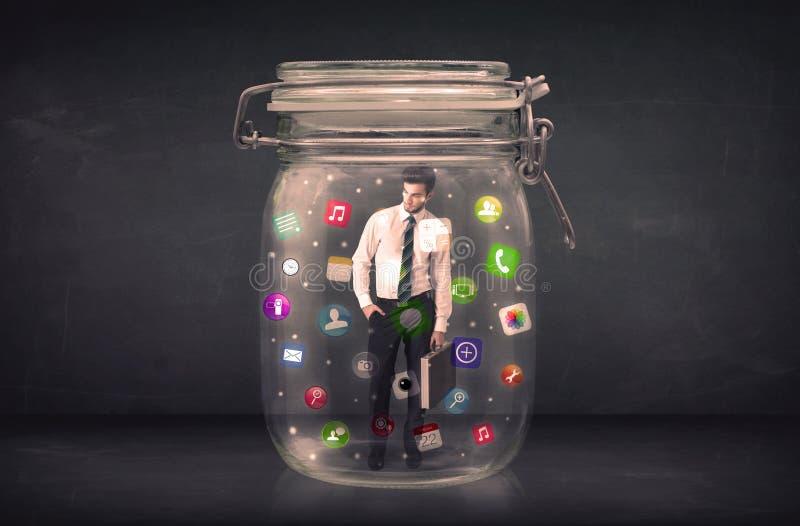 Affärsmannen som fångas i en glass krus med färgglade app-symboler, lurar arkivfoto