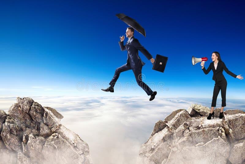 Affärsmannen som hoppar över en klippa och en kollega, hurrar med megafon royaltyfri foto