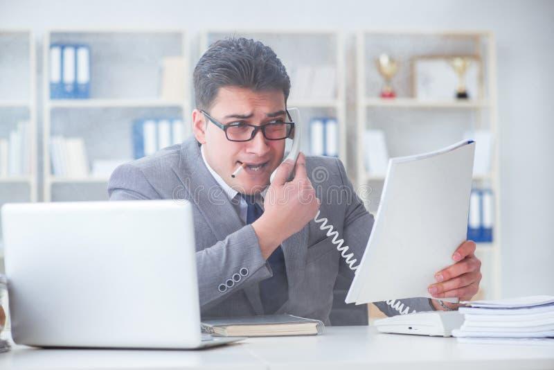 Affärsmannen som i regeringsställning röker på arbete arkivfoto