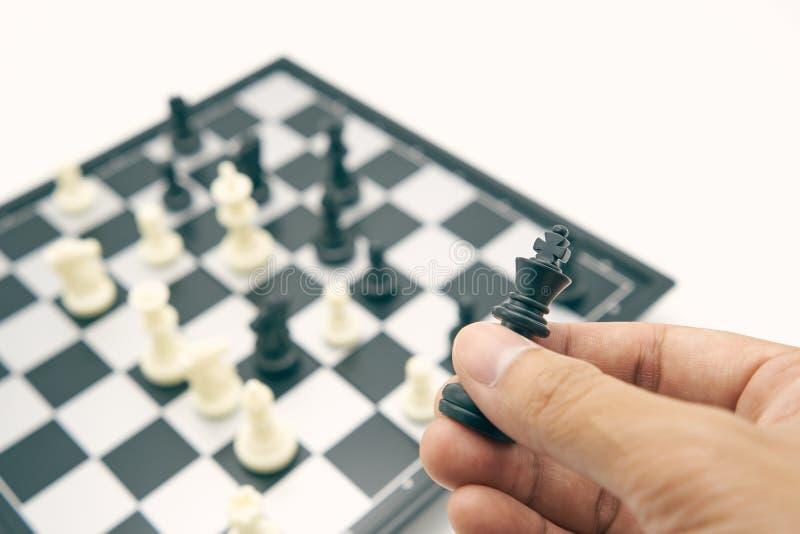 Affärsmannen som rymmer en konung Chess, förläggas på schackbräde använda som bakgrundsaffärsidé och strategibegrepp med kopierin fotografering för bildbyråer