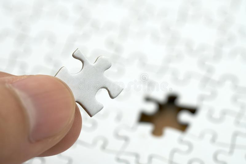 Affärsmannen som rymmer en vit figursåg, förläggas på en vit figursåg använda som bakgrundsaffärsidé och strategibegrepp med kopi arkivfoto
