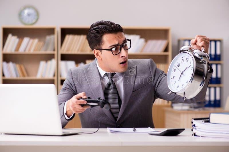 Affärsmannen som spelar dataspelar på arbetskontoret arkivfoto
