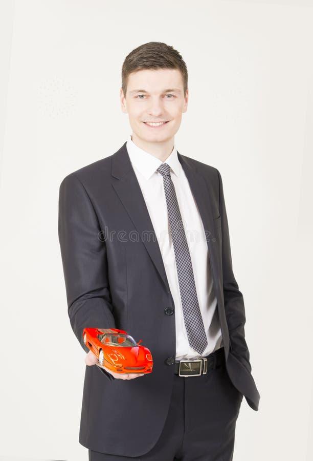 Affärsmannen som visar en leksakbil på hans, gömma i handflatan arkivfoton