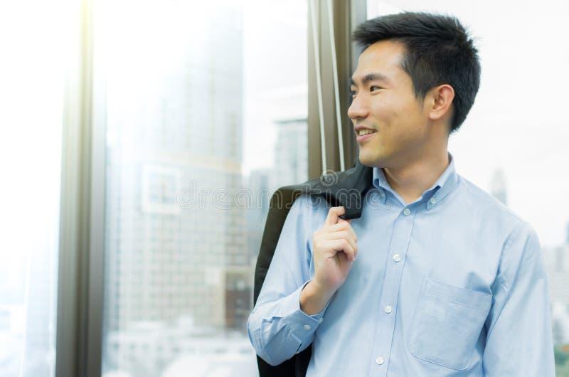 Affärsmannen står bredvid fönstret i kontoret arkivfoto