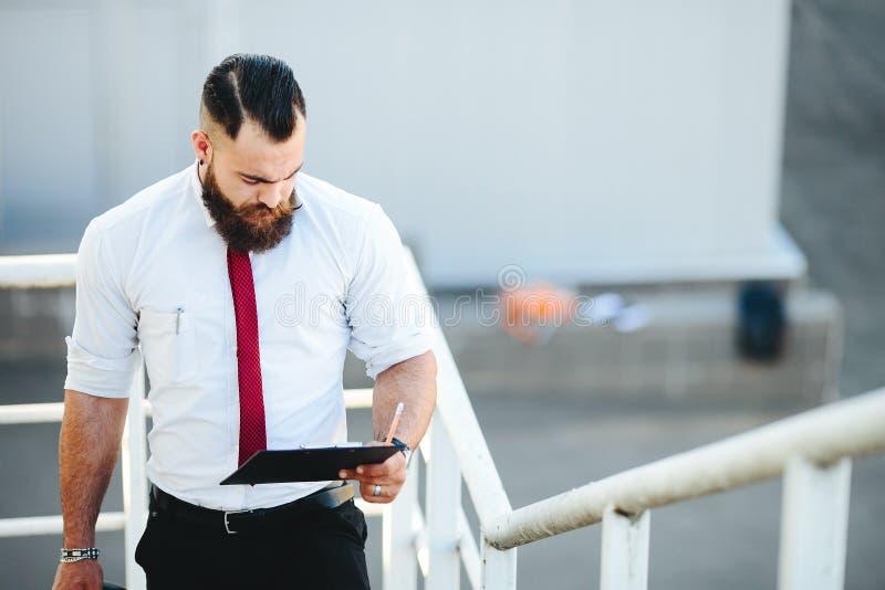 Affärsmannen står med dokument i hand arkivfoton