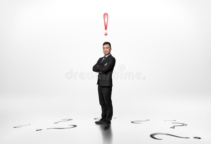Affärsmannen står med utropsteckenet ovanför honom och frågor på golv fotografering för bildbyråer
