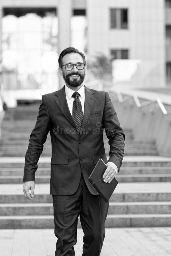 Affärsmannen står på kontorsbyggnad med minnestavlan i hand iklädd affärsdräkt för person och vit skjorta som går att göra affär arkivbilder