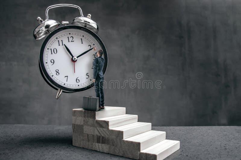 Affärsmannen står på trappa och försök för att ändra klockahanden arkivfoto
