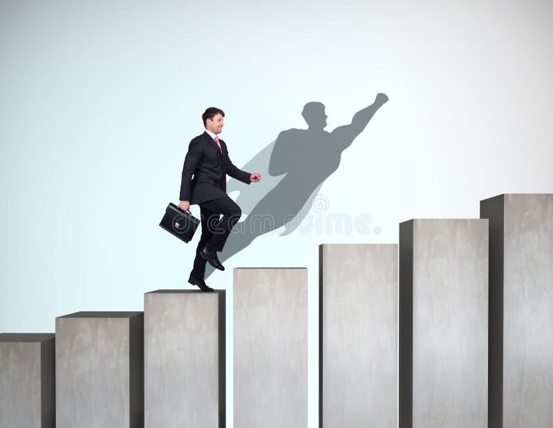 Affärsmannen stiger upp på karriärstegen med superheroskugga på väggen arkivbild