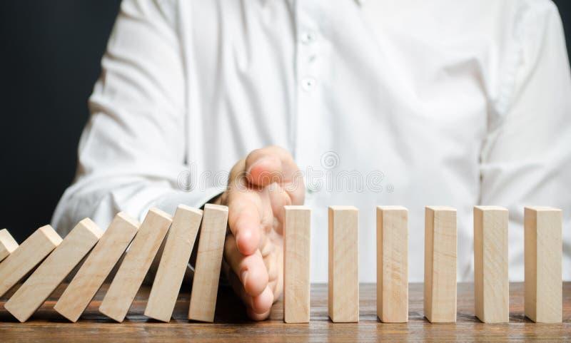 Affärsmannen stoppar att falla för dominobricka Begrepp f?r riskledning Lyckad stark affärs- och problemlösning Pålitlig ledare S arkivfoto