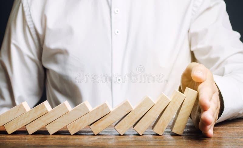 Affärsmannen stoppar att falla för dominobricka Begrepp f?r riskledning Lyckad stark affärs- och problemlösning Pålitlig ledare S arkivfoton