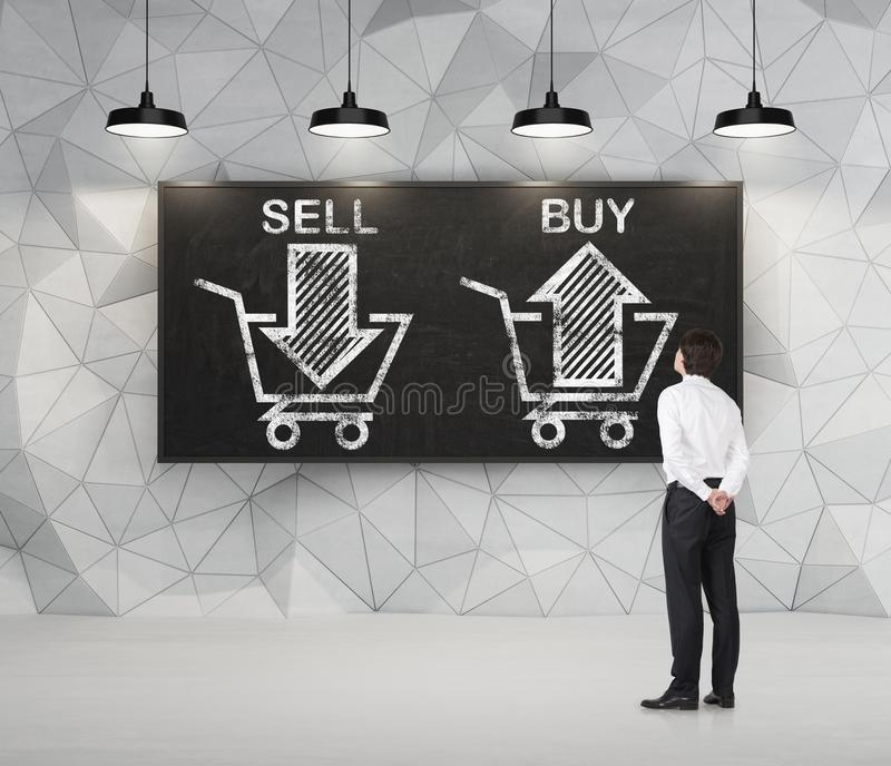 Affärsmannen tänker om den primaa 'försäljningen eller köpet', pilar på svart tavla fotografering för bildbyråer