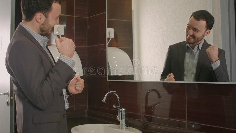Affärsmannen tar en blick på honom i spegeln arkivfoton